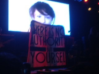 "(Penny Rimbaud holds up the recognizable Crass banner reading ""THERE IS NO AUTHORITY BUT YOURSELF"" in the final moments of their performance. August 7th, 2014.)"